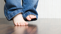 Child's bare feet on hard floor