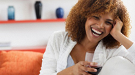 Woman with glass of wine, laughing
