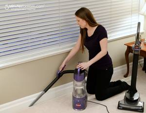 Woman vacuuming baseboards with extension tool