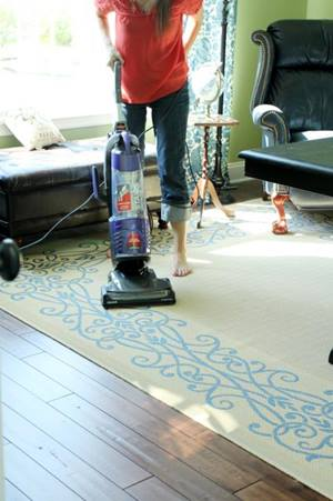 Woman vacuuming rug and hard floor