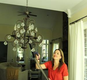 Woman vacuuming chandelier