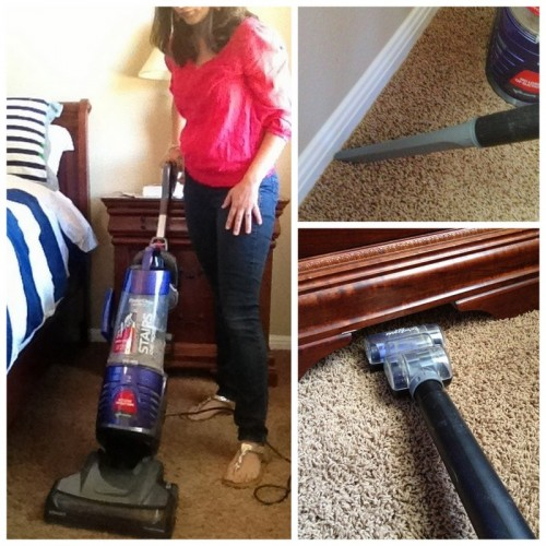 Woman vacuuming bedroom floor, in corners and under furniture