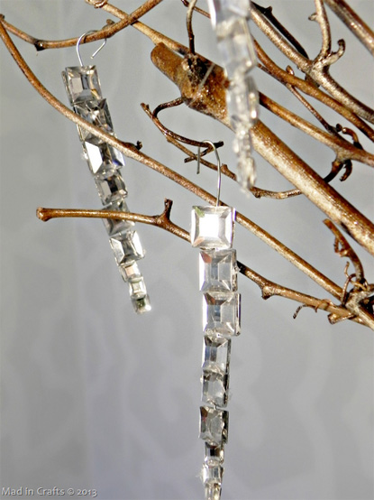 Faceted icicle ornament hanging on branch