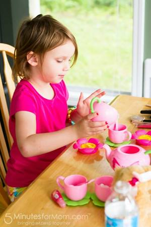 Little girl with play tea set
